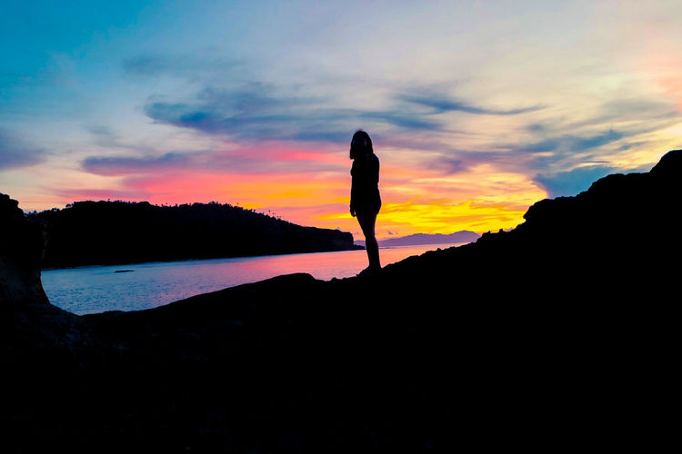 Silhouette woman standing on shore against sky during sunset