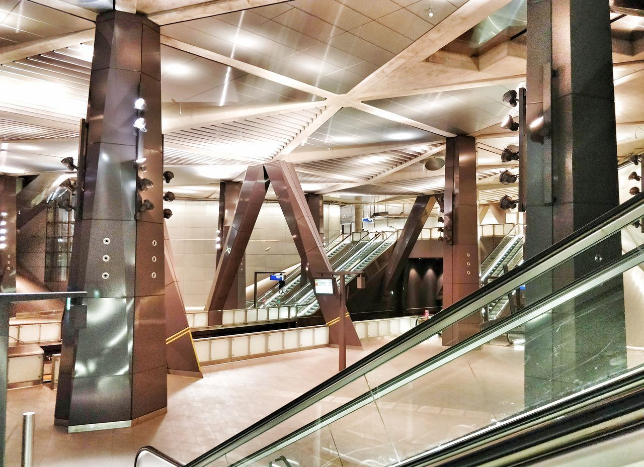 indoors, architecture, escalator, glass - material, built structure, transportation, modern, no people, staircase, architectural column, public transportation, illuminated, rail transportation, railing, technology, mode of transportation, absence, empty, transparent, reflection, ceiling, subway train, moving walkway