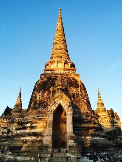 Low angle view of stupa at wat phra sri sanphet against clear blue sky