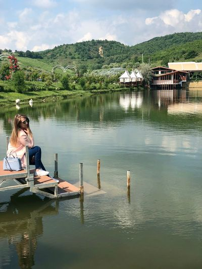 Woman Sitting On Steps By Lake
