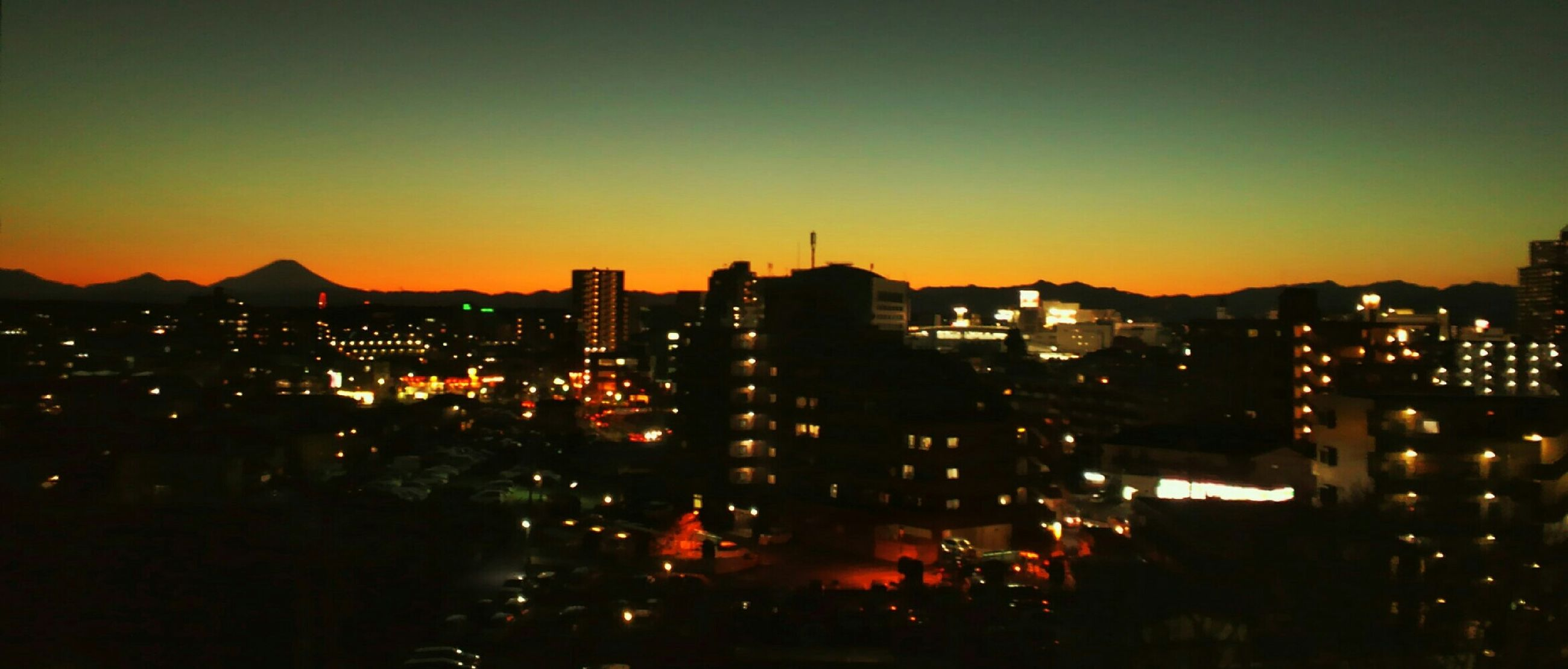 illuminated, building exterior, city, cityscape, sunset, architecture, built structure, copy space, high angle view, clear sky, night, orange color, city life, residential district, crowded, dusk, residential building, residential structure, sky, silhouette