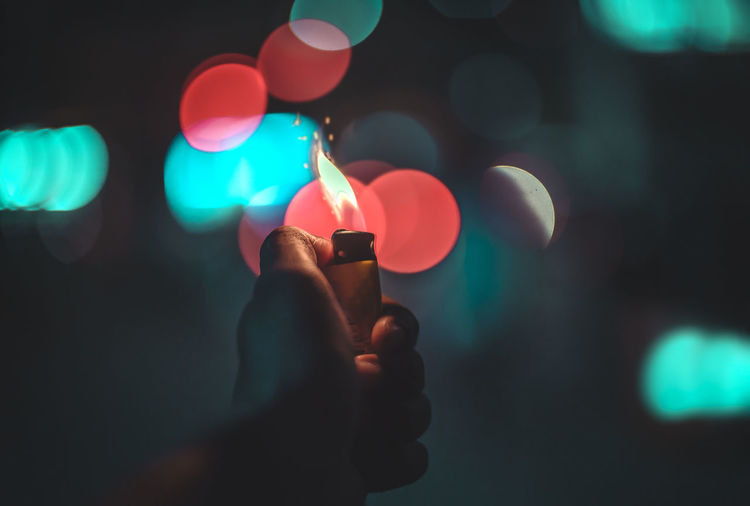 Close-Up Of Human Hand Holding Illuminated Cigarette Lighter Against Illuminated Lights