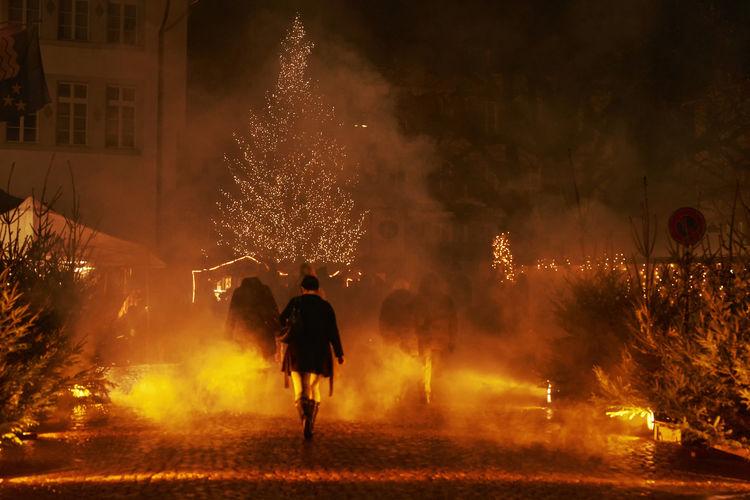 Rear view of woman walking at christmas market at night