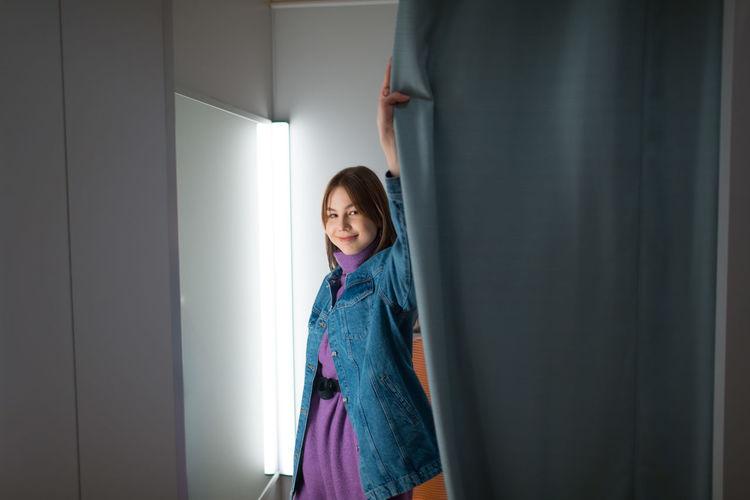 Smiling girl standing against door