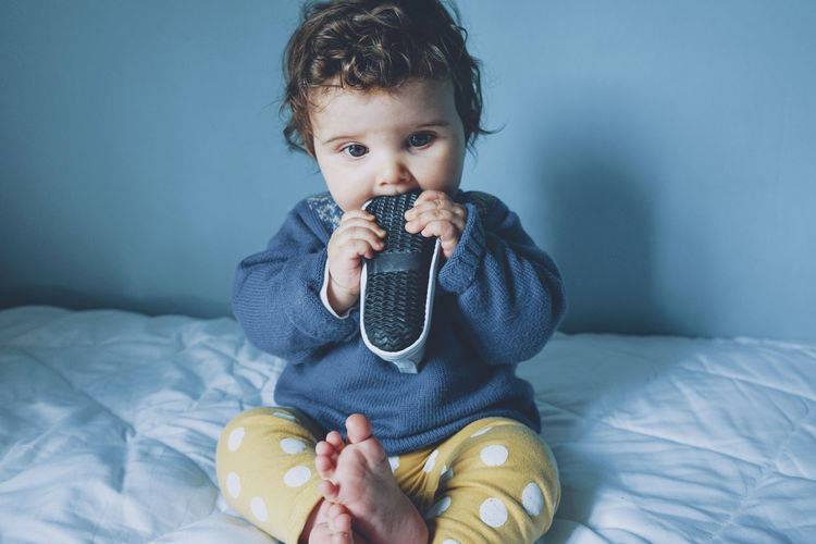 Cute boy holding baby on bed at home