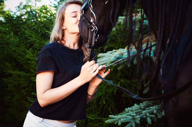 Young woman kissing horse while standing by trees