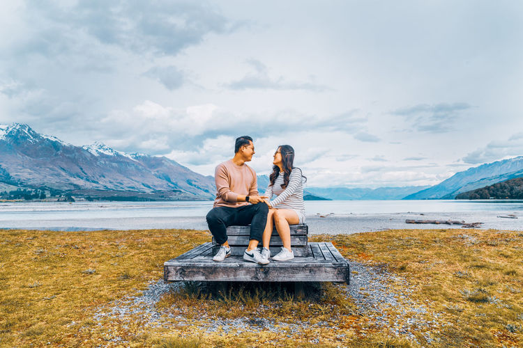 Young couple sitting on shore against sky
