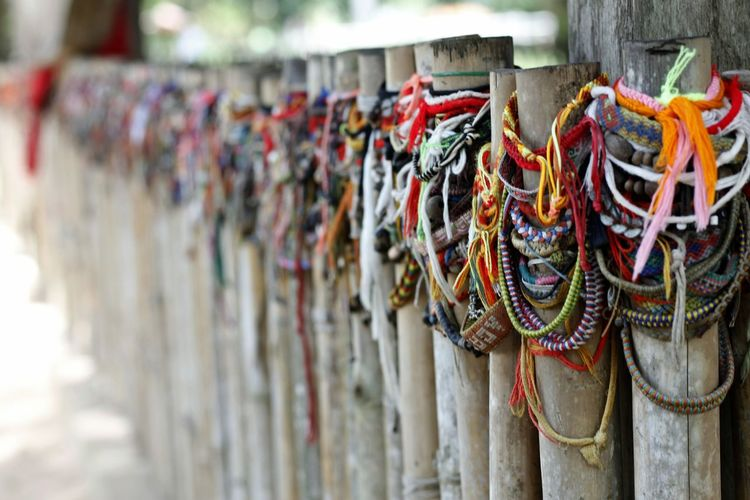 Close-up of colorful strings tied on wooden posts