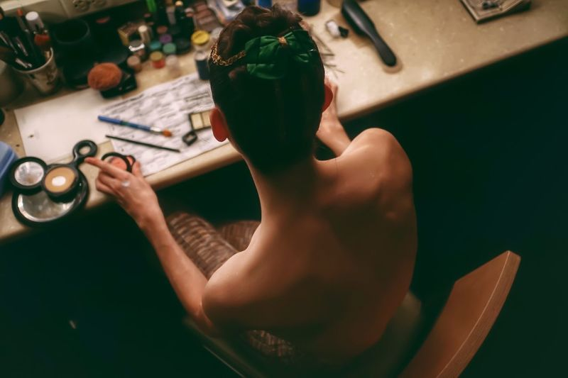 High Angle View Of Shirtless Ballet Dancer Sitting On Chair In Dressing Table
