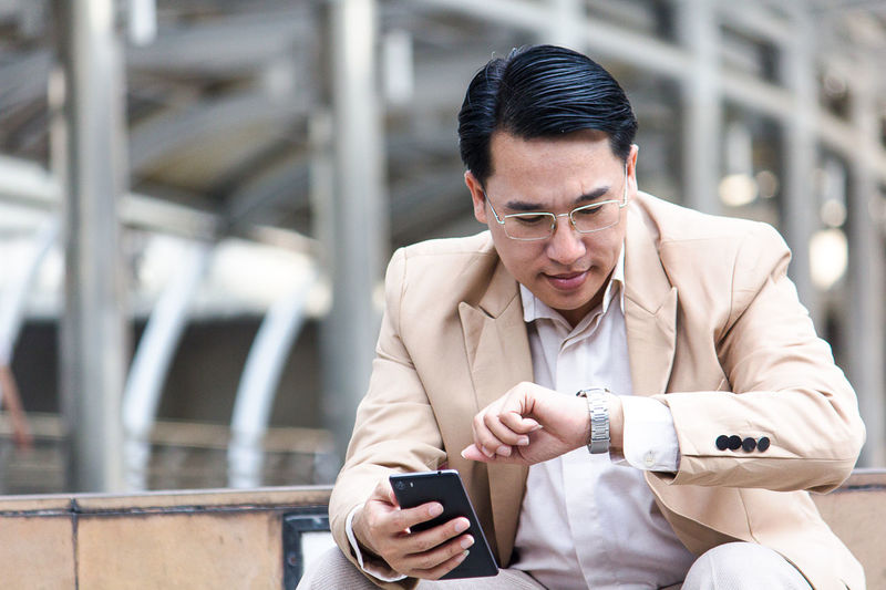 Black Hair Businessman Communication Connection Day Focus On Foreground Front View Holding Looking Down Mobile Phone One Person Outdoors People Portability Portable Information Device Real People Smart Phone Standing Technology Text Messaging Using Phone Well-dressed Wireless Technology Young Adult