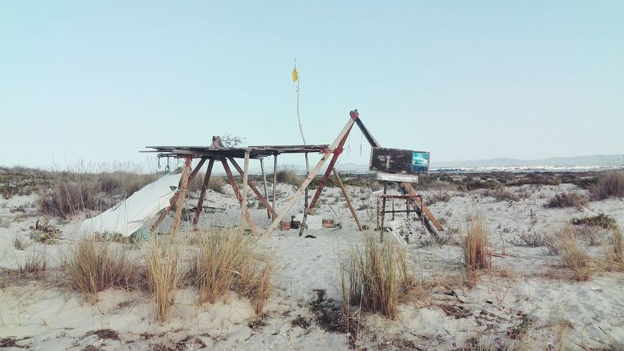 Abandoned Wooden Structure At Sandy Beach Against Clear Sky