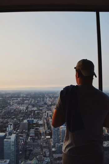 Rear view of man standing by window while looking at cityscape against clear sky