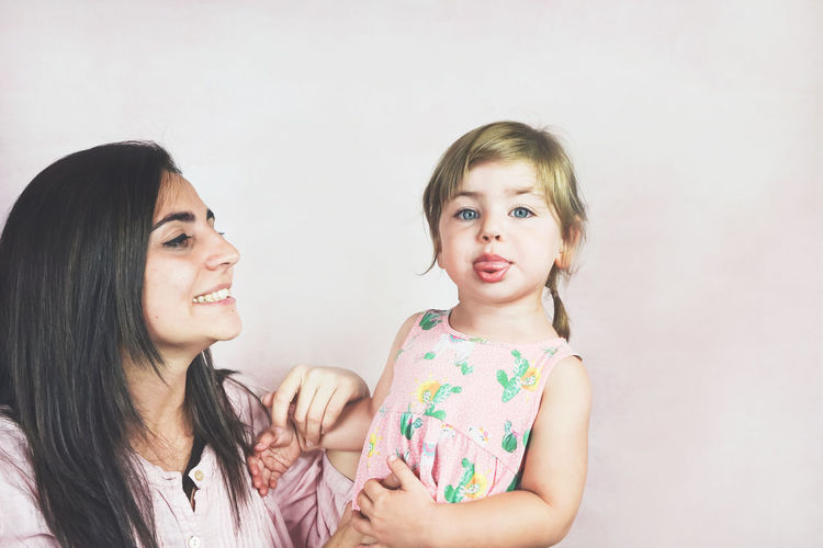 Two People Women Child Childhood Females Girls Togetherness Family Portrait Smiling Indoors  Emotion Headshot Hair Adult Happiness Studio Shot Bonding Innocence Hairstyle Daughter Positive Emotion Sister Bangs Sticking Out Tongue
