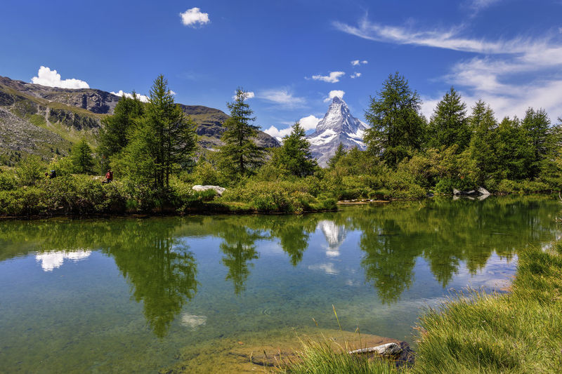 Panoramic view of Swiss Alps and Matterhorn Mountains near Zermatt area. Small lake in the middle of the mountains with beautiful mountain reflection in it , Switzerland Matterhorn  Reflection Beauty In Nature Cloud - Sky Day Idyllic Lake Lake View Mountain Nature No People Non-urban Scene Outdoors Plant Reflection Scenics - Nature Sky Swiss Swiss Alps Switzerland Tranquil Scene Tranquility Tree Water Waterfront