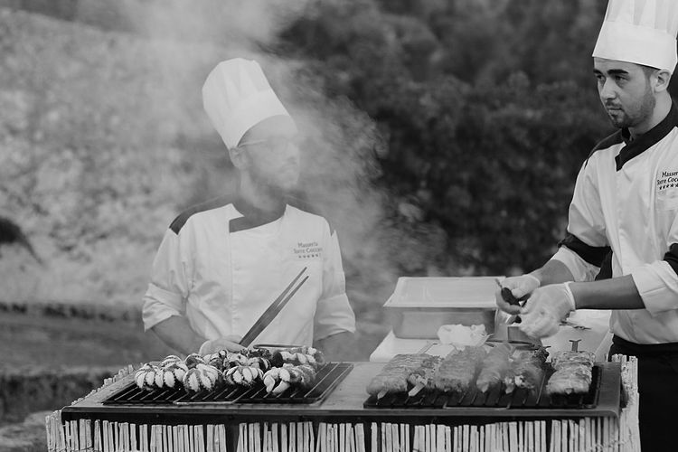 Chefs cooking food on barbeque grill at restaurant