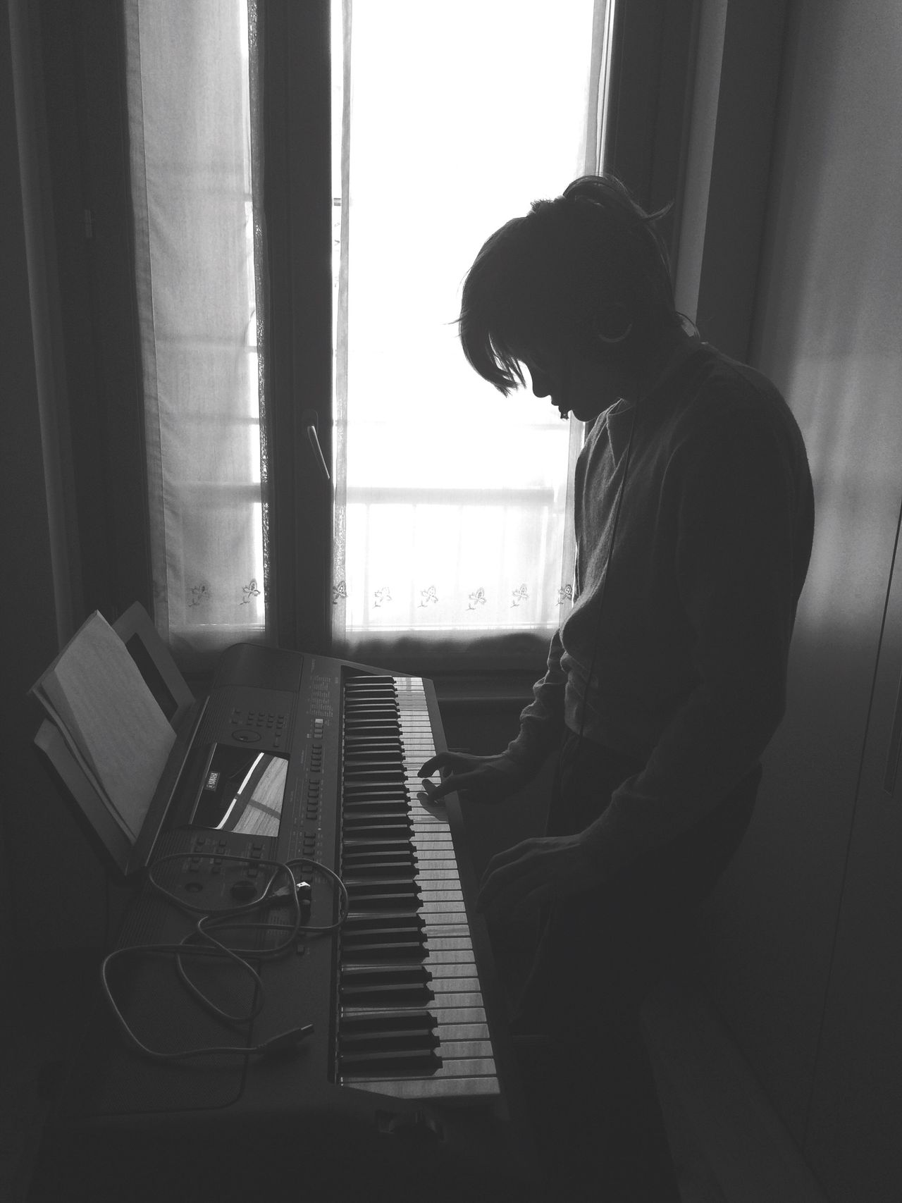 Side view of silhouette boy playing piano while standing at home