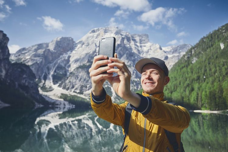Smiling hiker taking selfie through mobile phone against lake and mountains