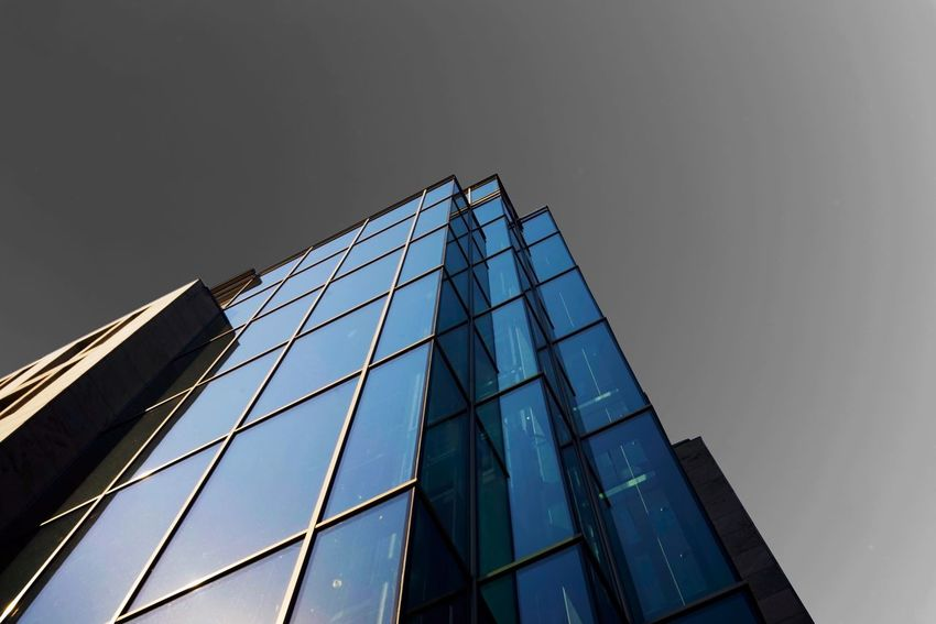 Low Angle View Built Structure Sky Architecture Building Exterior Building Clear Sky No People City Office Building Exterior Modern Glass - Material Day Office Outdoors Tall - High Pattern Sunlight Construction Industry