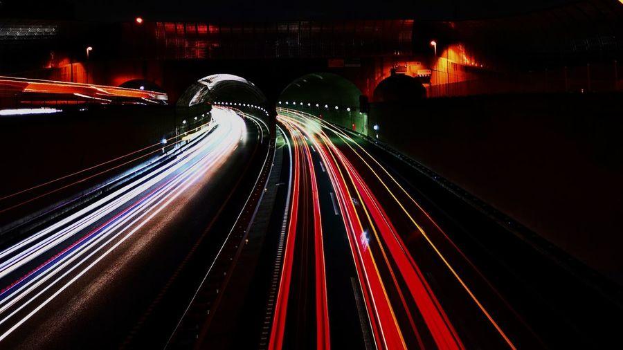 Light trails on illuminated bridge at night