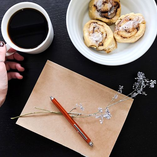 High angle view of coffee and notebook on table