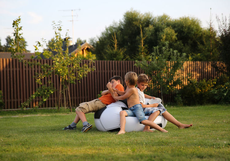 Boys Playing On Bean Bag In Yard