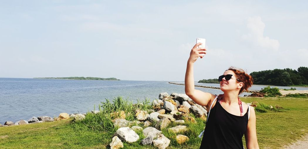 Woman taking selfie against sea