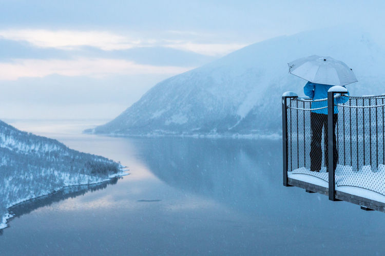 Beauty In Nature Bridge Cold Temperature Day Fjord Fjords Frozen Lake Mountain Nature Northern Norway Norway One Person Outdoors Rear View Reflection Scenics Sky Snow Snowing Tranquil Scene The Great Outdoors - 2017 EyeEm Awards Umbrella Water Winter