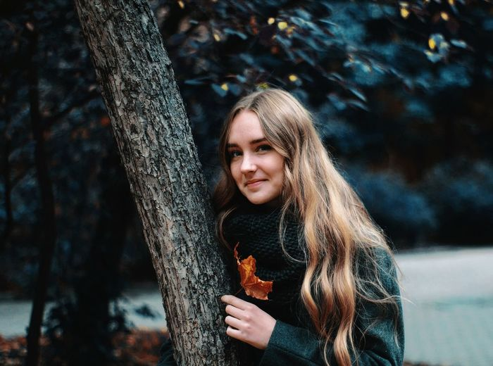 Portrait of beautiful young woman against tree trunk