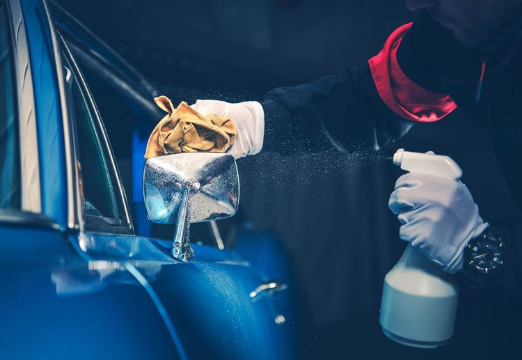 Midsection Of Man Cleaning Car In Workshop