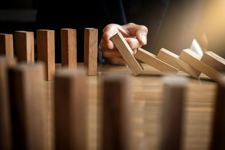 Cropped hand playing with wooden dominoes on table