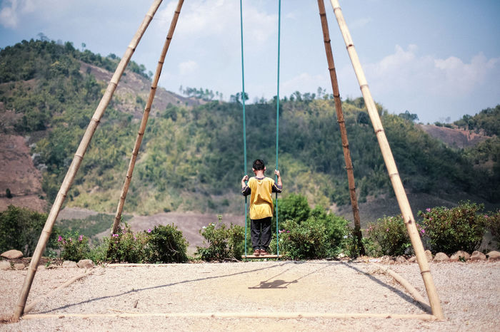 Mae Salong, Golden Triangle area in Northern Thailand. Local boy playing at a giant swing, used by a local Akha tribe for the traditional and spiritual activities. Akha Balance Boy Chiang Rai Day Golden Triangle Horizontal Mae Salong Mountains Nature One Person Outdoors People Person Playing Sky Spiritual Suspension Bridge Swing Thailand Tradition Tranquility Tribal Tribe Two People
