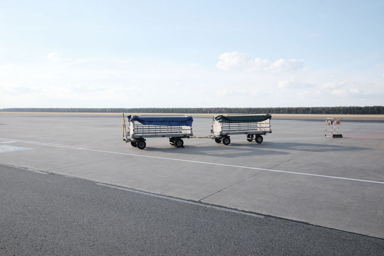 luggage trolley at the airport Service Trolley Air Vehicle Airplane Airport Airport Runway Asphalt Baggage Business Carriage Cloud - Sky Day Empty Freight Transportation Land Vehicle Mode Of Transportation Outdoors Semi-truck Sky Transportation Travel Truck Wheel