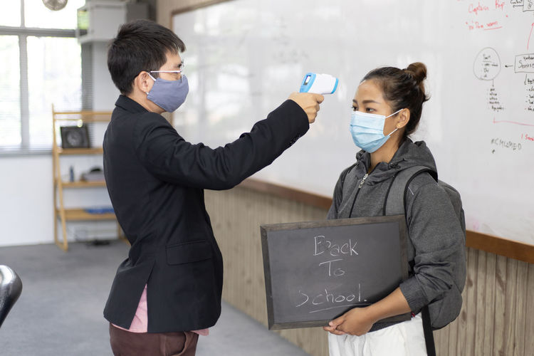 Side view of man wearing flu mask checking temperature of woman at school