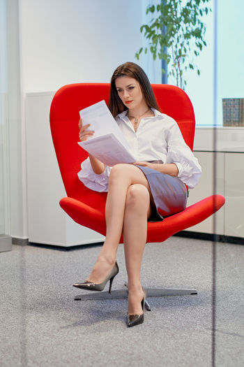 Businesswoman examining documents while sitting on chair in office