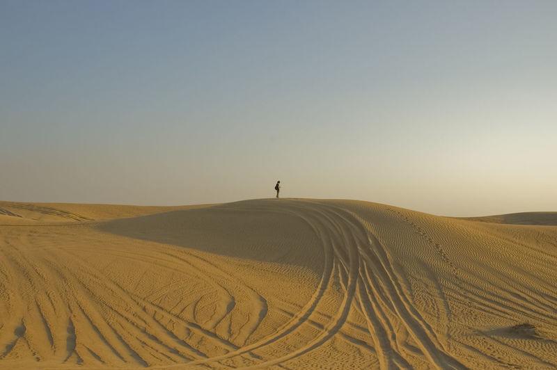 Tire tracks in desert against clear sky