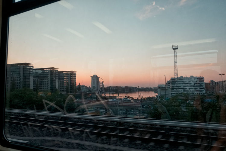View of bridge and buildings against sky at sunset