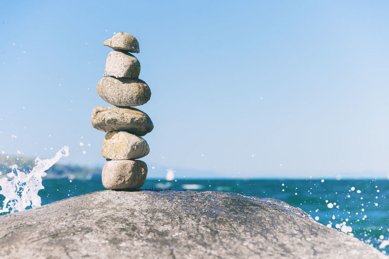 Stack of stones by sea against sky