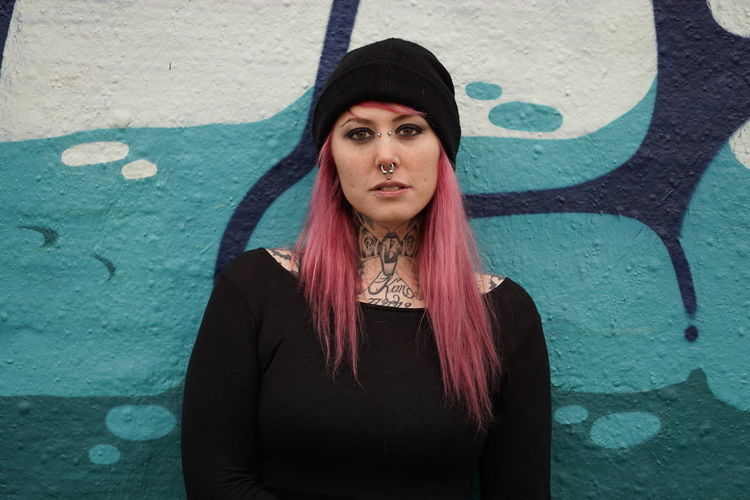 Portrait of smiling woman with pink hair standing against graffiti wall