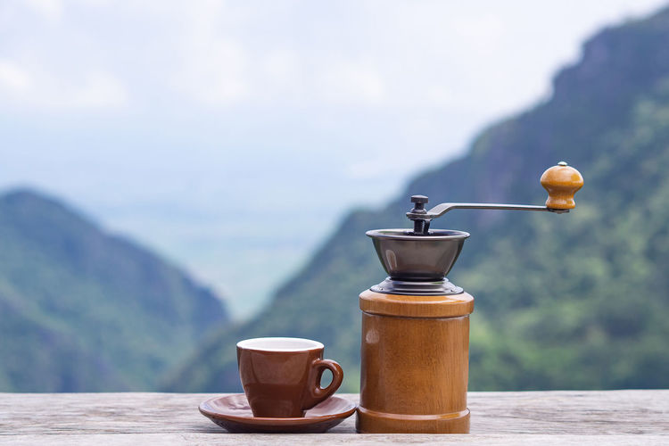 Manual coffee grinder and a coffee cup on wooden table with beautiful scenery view of mountains.