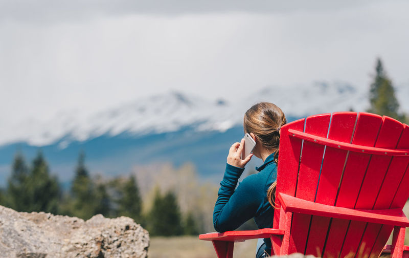 Rear view of woman using smart phone while sitting on chair against snowcapped mountain