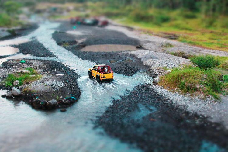 Tilt shift image of car in water in road