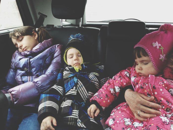 Siblings wearing warm clothing while sleeping in car