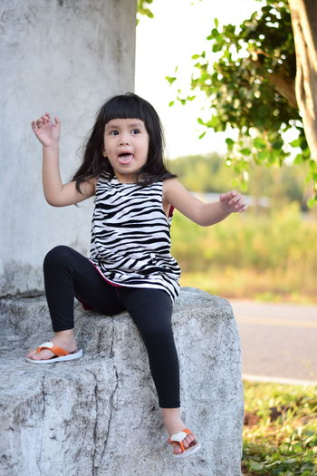 Cute girl sitting on built structure