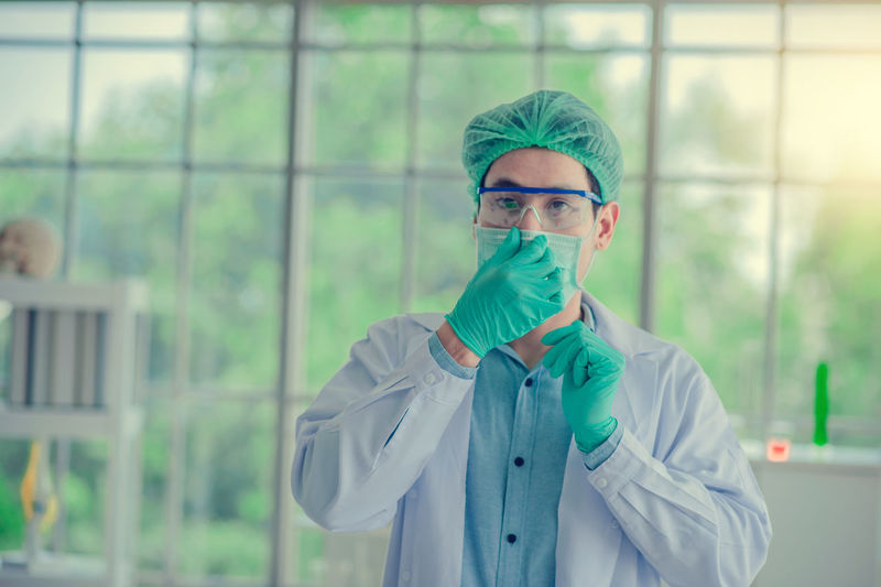 Portrait of scientist wearing surgical mask and cap standing in laboratory