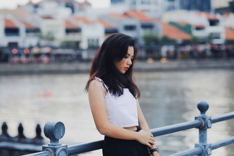 Side view of thoughtful young woman standing on footbridge by river