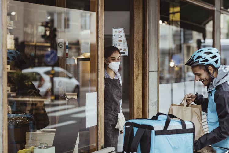 People enjoying at glass window of store