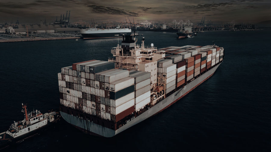 Photographs of container ships and tugboat floating at sea for the import and export