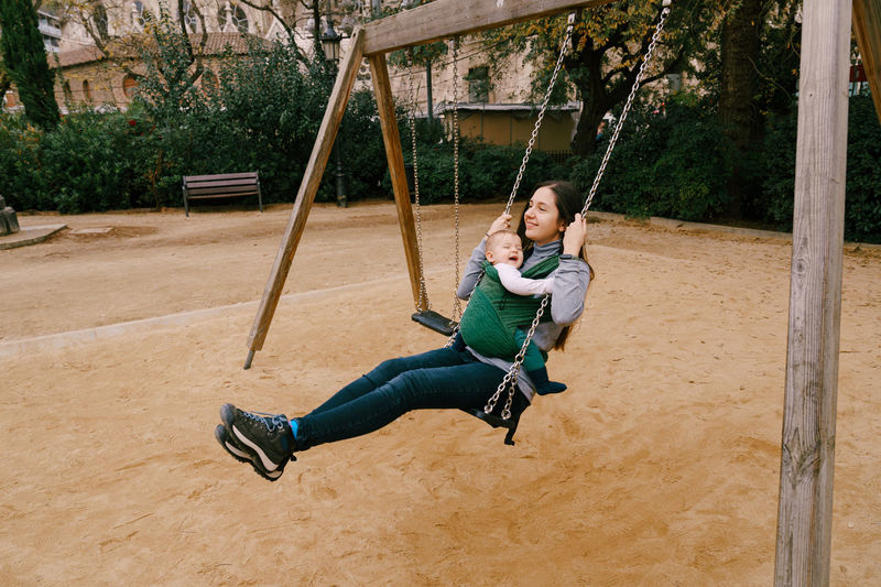 Full length of smiling boy on swing at playground