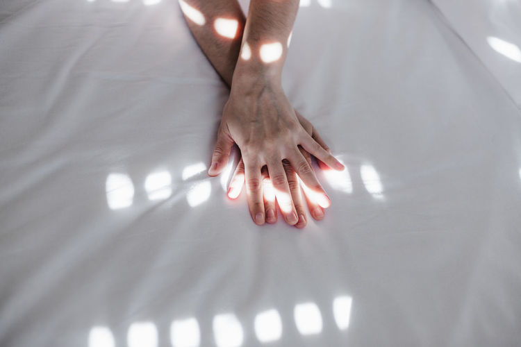 Low section of woman walking on bed