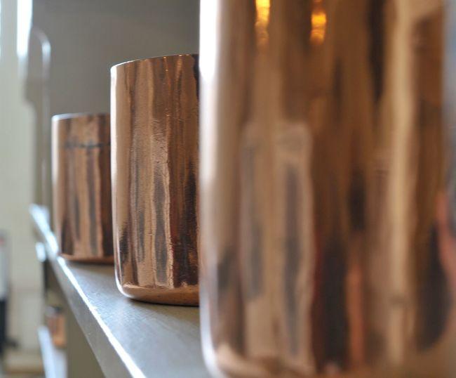 Copper pots on a shelf in a grand kitchen